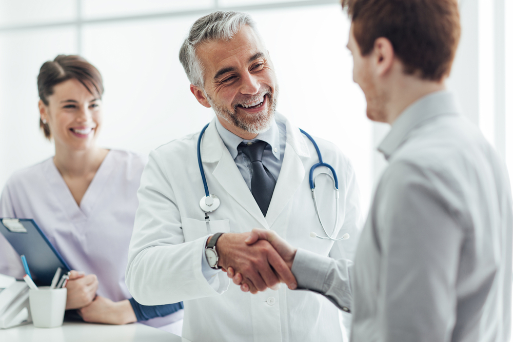 A male doctor and patient shaking hands.