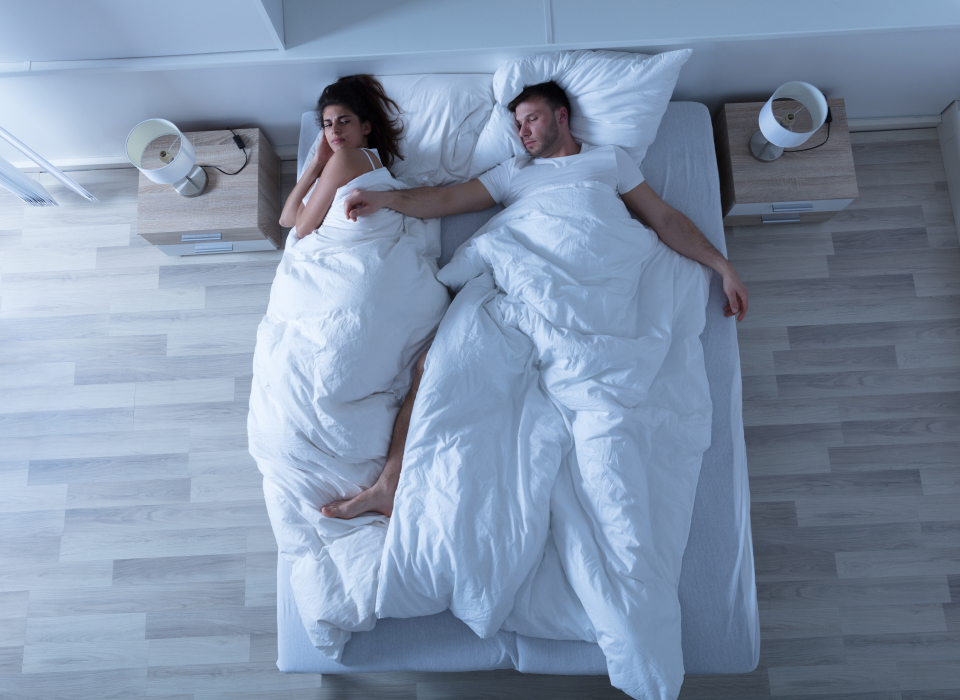 couple sleeping in bed while woman looks uncomfortable